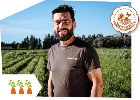 Portrait d'un producteur de carottes de Provence dans son champ, accompagné du logo du label Haute Valeur Environnementale superposé sur l'image.